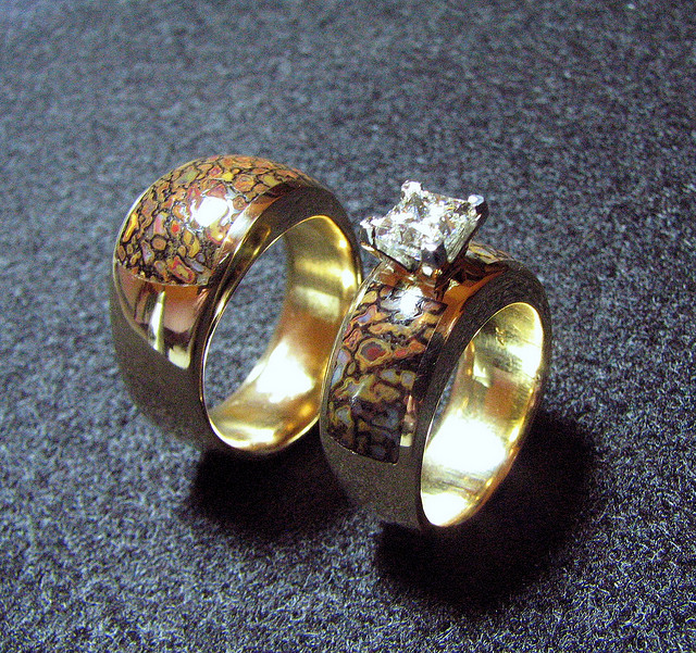 "A wedding ring set featuring dinosaur bone inlays on gold.  Some dinosaur bones were fossilized as gem-quality minerals, like chalcedony or opal, referred to as ""gembones.""  ""14k Gembone Wedding Set"" by Jessa and Mark Anderson is licensed under CC By 2.0"