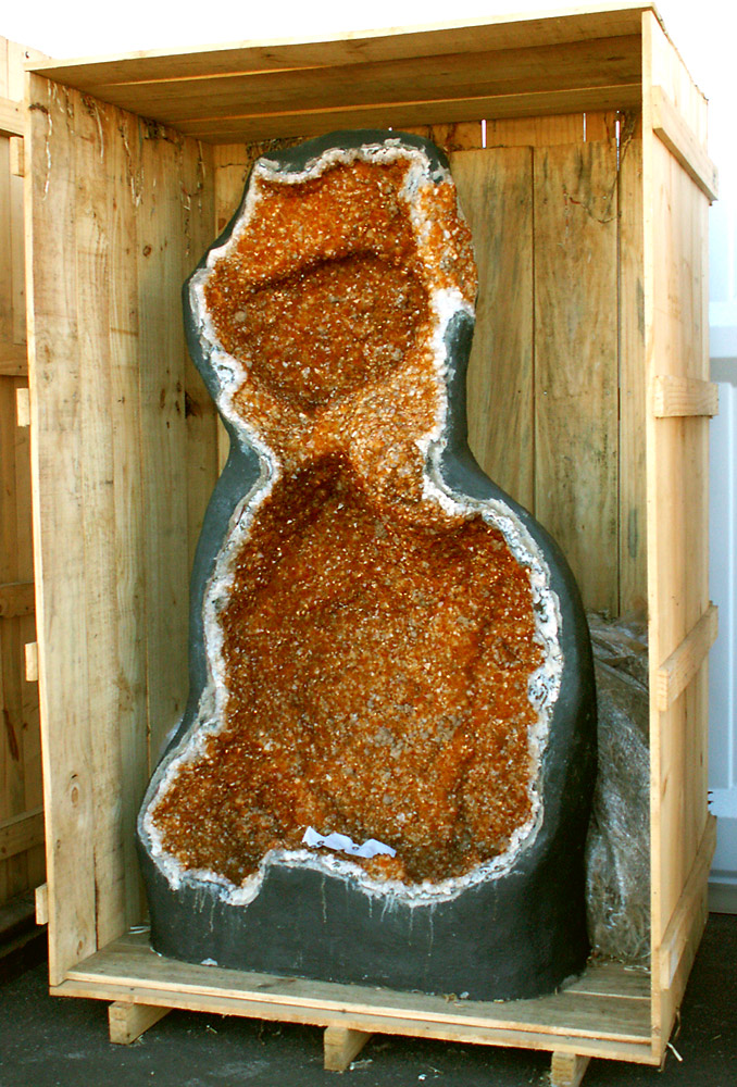 "This citrine vug is in a crate about 9' tall. ""Large Crated Vug, Tucson"" by cobalt123 is licensed under CC By-SA 2.0"