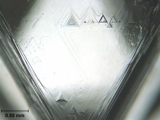 "Trigon inclusions are part of a natural, uncut diamond's original crystal structure. These were photographed on the surface of a rough diamond through a microscope. If trigons are found on a faceted gemstone girdle, it's a good indication the stone is a natural diamond. Identifying inclusions is just one step in the process of identifying gemstones. ""Diamond Face Trigons Scale"" by Gump Stump is licensed under CC By-SA 3.0"