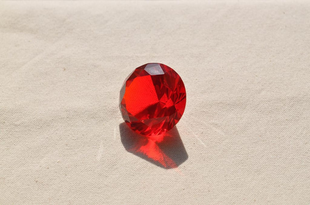 "Some synthetic gemstones are clearly labeled as such.  Dangers arise for gem buyers when gems are labeled incorrectly in the marketplace, whether in error or deliberately.  ""Ruby (Fake)"" by maicos is licensed under CC By 2.0"