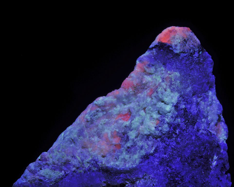 "Crystals of tugtupite under LW UV light.  Collectors value this mineral, found in Greenland, for its intense gemstone luminescence. ""Tugtupite"" by Parent Géry is licensed under CC By-SA 3.0"