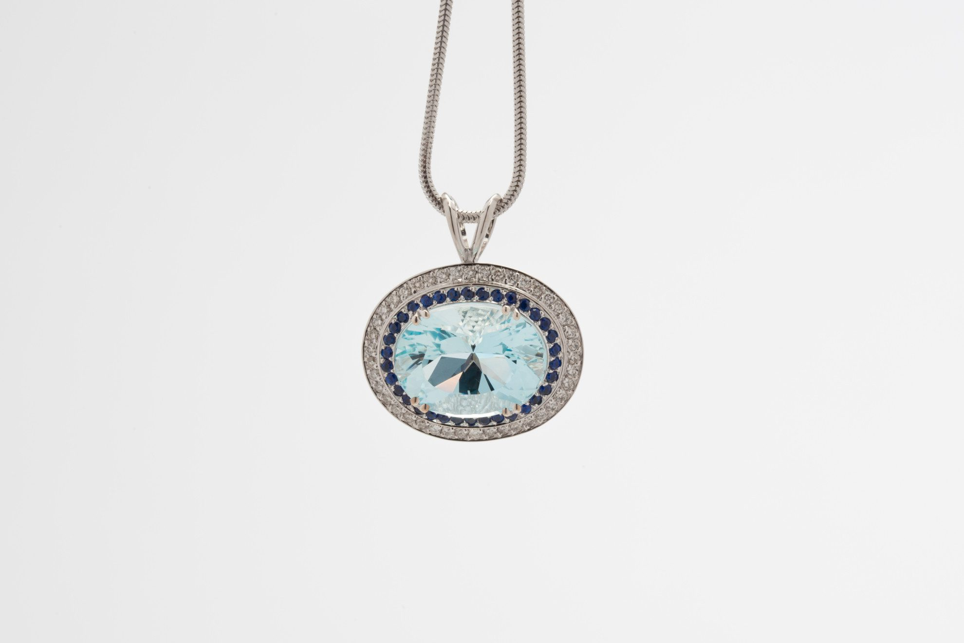 Re-Cut Aquamarine set into a pendant with sapphires and diamond melee