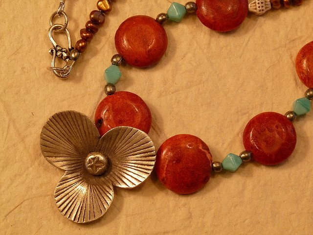 """Sea Blossom Necklace - Pendant and Clasp Detail,"" Bali silver, coral coins, and bronze pearls, by Christopher, Tania and Isabelle Luna is licensed under CC By 2.0"