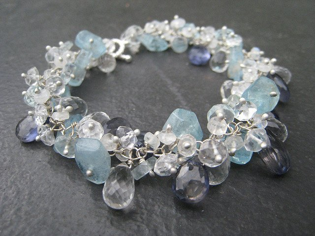 "This bracelet, inspired by the colors of Antarctica, features iolites, moonstones, rock crystals, and chunks and disks of pale blue aquamarine. ""Glacial Bracelet"" by Marianne Madden is licensed under CC By-SA 2.0"
