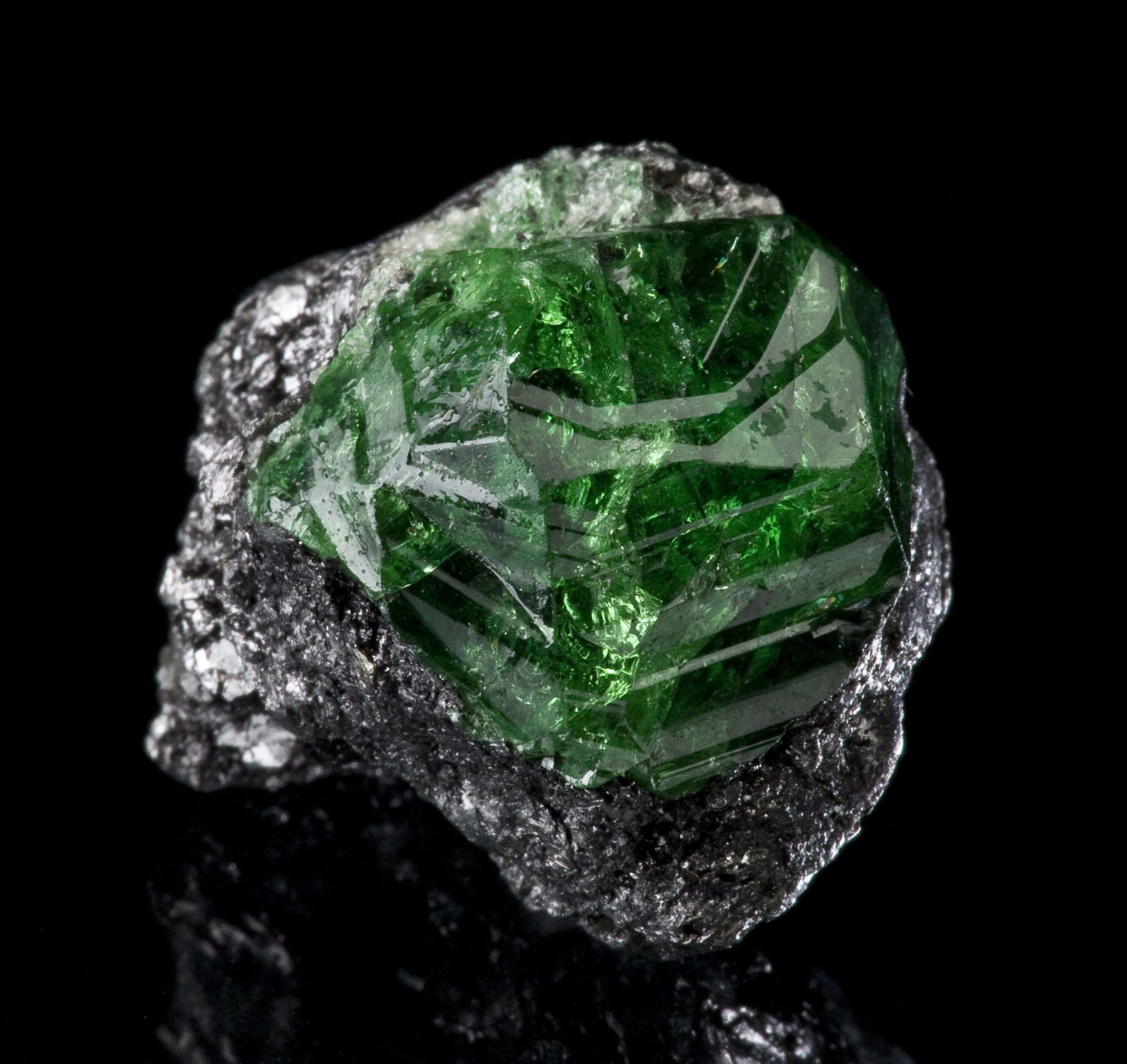 """Tsavorite Garnet on graphite,"" Merelani Hills, Lelatema Mts, Arusha Region, Tanzania. © Rob Lavinsky, www.iRocks.com. Used with permission."