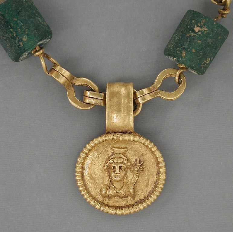"This Egyptian necklace dates from 30 BCE – 300 CE and features green glass beads. ""Gold Necklace with Medallion Depicting a Goddess LACMA 50.22.20."" Public Domain."