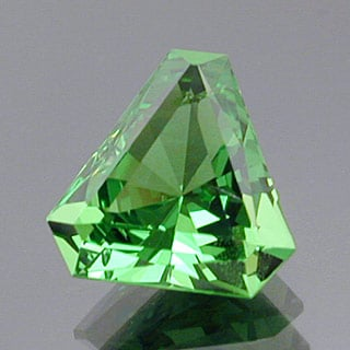 "Although not recommended for a garnet with a dark tone, a Barion cut brings out the brilliance in this light-green garnet gem. ""Tsavorite Garnet."" Elongated, cut-cornered Barion triangle cut. ©Dan Stairs Custom Gemstones. Used with permission."