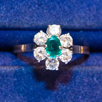 "The emerald in this 1960s ring has been damaged over time. ""My Mother's Daisy Setting (Top-Down)"" by Erik Ogan is licensed under CC By-SA 2.0. (Cropped to show detail)."