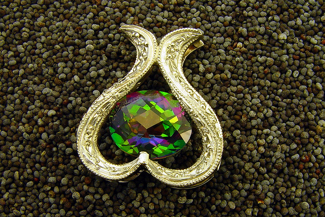 "A mystic topaz is an enhanced topaz gemstone. The vapor deposition process creates a multicolor surface coating on the stone. ""Tulip (1),"" 14kt white gold pendent with mystic topaz, by Mark Somma is licensed under CC By 2.0"