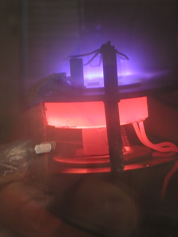 """""""PICT0111.JPG,"""" DC-PECVD system in action. DC plasma (violet) improves the growth conditions for carbon nanotubes in this chemical vapor deposition chamber. A heating element (red) provides the necessary substrate temperature, by Polyparadigm. Public domain."""