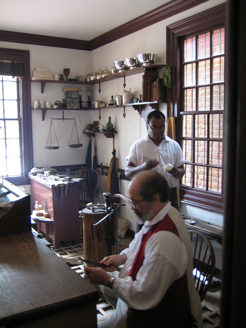 "Jewelers in Colonial Williamsburg, Virginia, using colonial era methods and tools. ""Virginia Trip - August 2012 019"" by Bob is licensed under CC By 2.0"