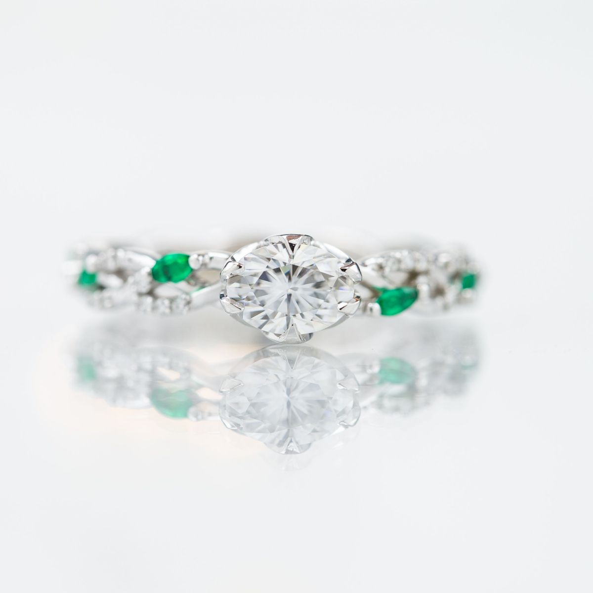 oval moissanite with emerald accents